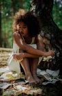 Traurige Frau mit zerrissenen Seiten im Wald — Stockfoto
