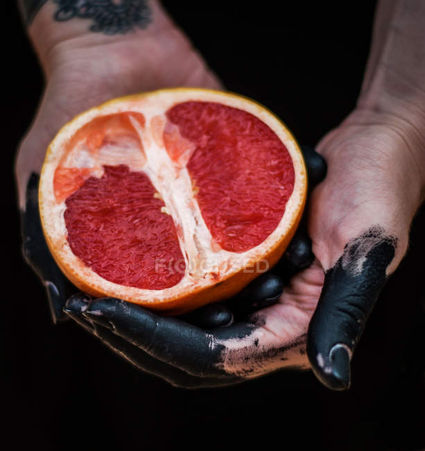 Femelle mains tenue pamplemousse — Photo de stock