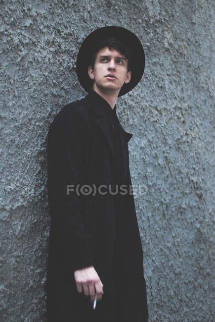 Uomo elegante che indossa cappotto lungo e cappello — Foto stock