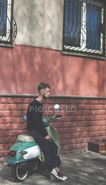 Young man sitting on vintage moped — Stock Photo