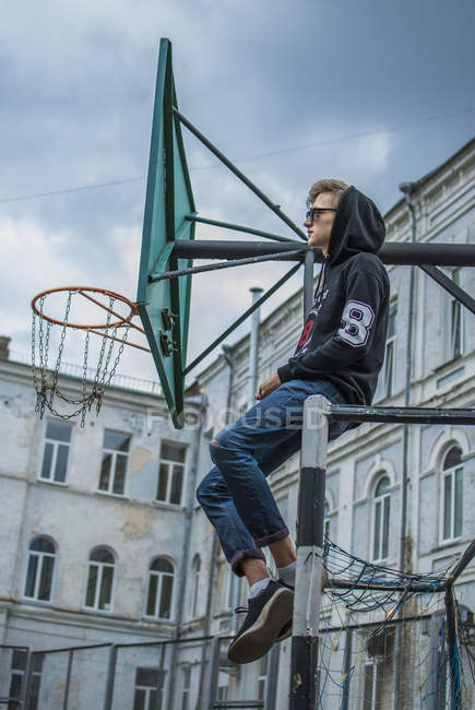 Hipster homme assis sur le terrain de basket en plein air — Photo de stock