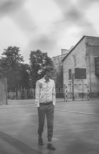 Hipster man standing on basketball court — Stock Photo