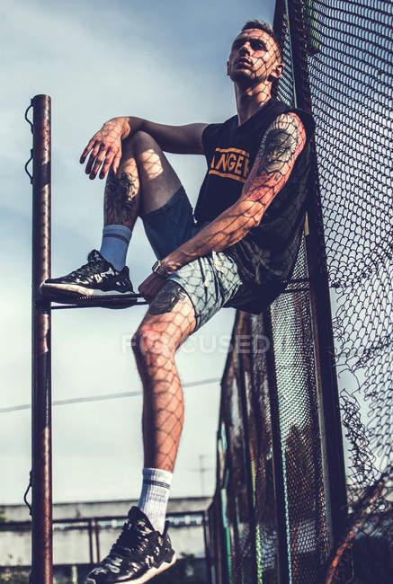 Татуйовані людини, що сидить на металеві конструкції — стокове фото