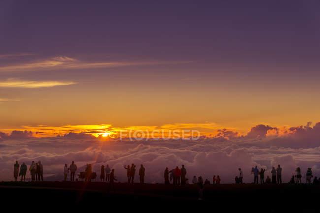 Gran puesta de sol sobre las nubes y multitud de personas en el Parque Nacional de Haleakal, este volcán de Maui, Hawaii, Estados Unidos - foto de stock