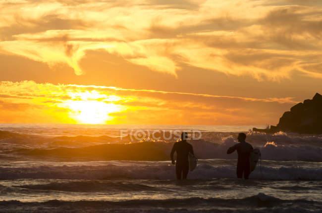 Surfisti in acqua con il tramonto sulla spiaggia in Australia — Foto stock