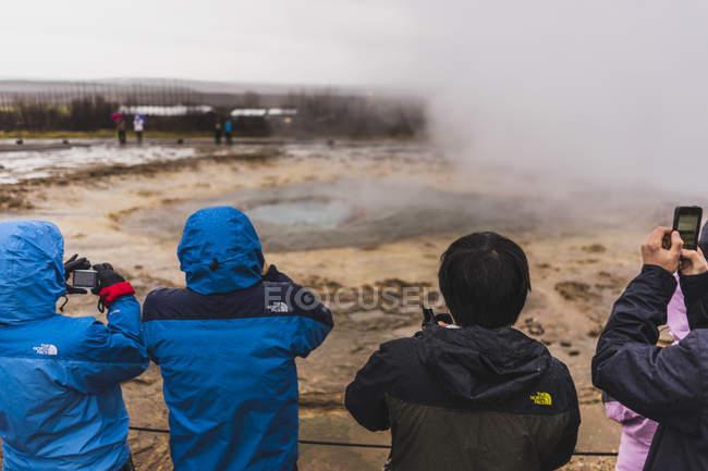 Personnes qui cherchent à geysir en imperméables au cours de la journée, Islande, Europe — Photo de stock