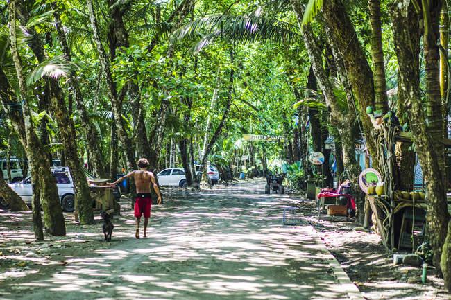 Homem de Bermuda vermelha andando ao lado de praia debaixo de árvores, Dominical, Costa rica, América Central 2015 — Fotografia de Stock
