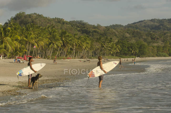 Beach in Santa Teresa and surfers with boards in front of water, Costa Rica — Stock Photo