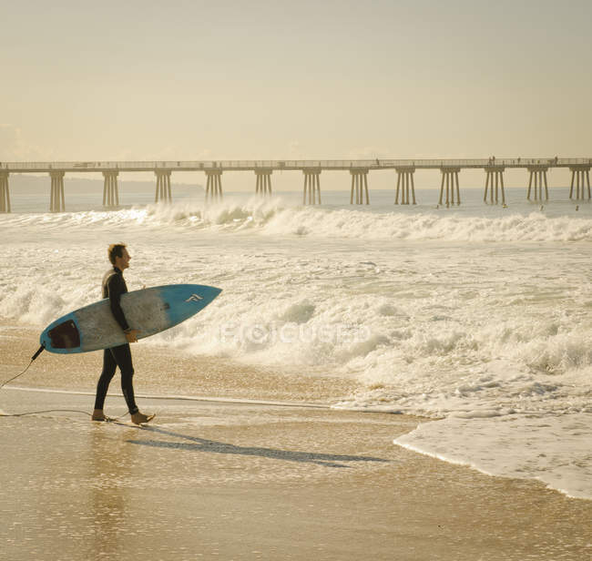 Surfer walking along beach with wavy waterin Los angeles, California, USA — Stock Photo