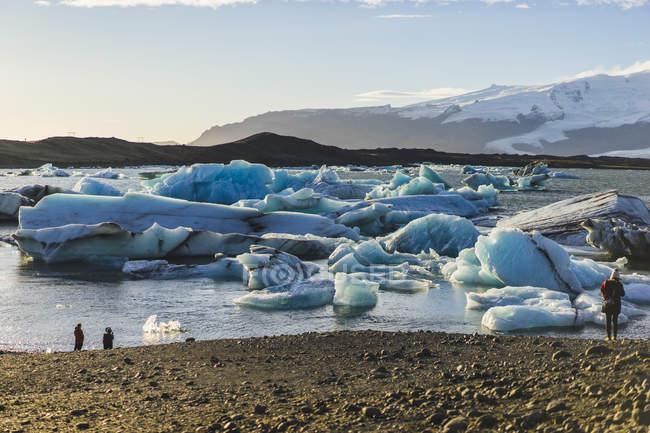 Des formations dans le lac avec les montagnes sur le fond et la foule des gens de la glace pendant la journée, Jokulsarlon, Islande, Europe — Photo de stock