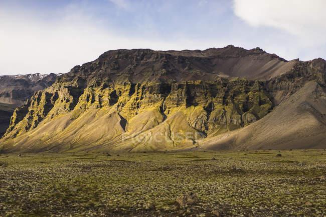 Rocky mountain avec une herbe verte sur le fond au cours de la journée, Skaftafell, Islande, Europe — Photo de stock