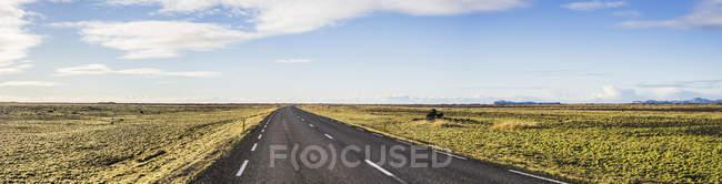 Vista da estrada de asfalto, rodeada por grama durante o dia, enquanto viaja ao redor da Islândia, Europa — Fotografia de Stock