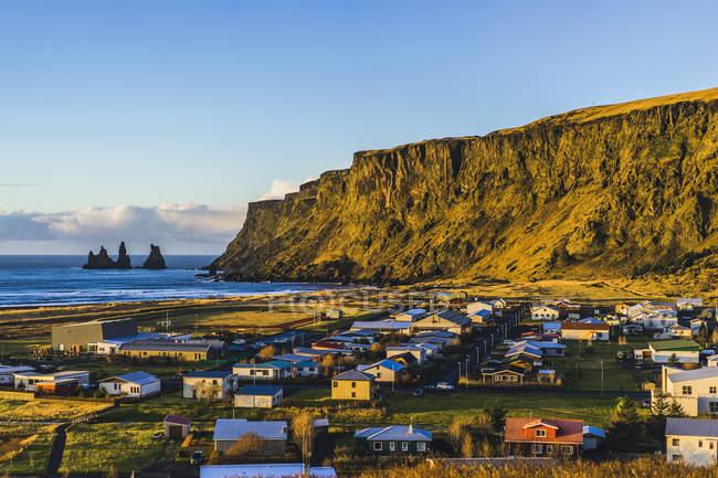 Vue sur montagne rocheuse avec des bâtiments sur la côte au bas, lever de soleil à Vik, Islande, Europe — Photo de stock