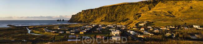 Vue de la falaise et maisons en bas au lever du soleil à Vik, Islande, Europe — Photo de stock