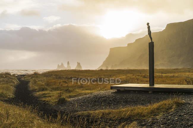 Montagne rocheuse sur le fond et l'homme statue au premier plan en Europe de Vik, Islande, — Photo de stock