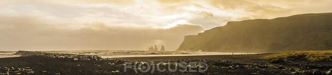 Montagne rocheuse sur le fond et les pierres sur la plage au premier plan au lever du soleil à Vik, Islande, Europe — Photo de stock