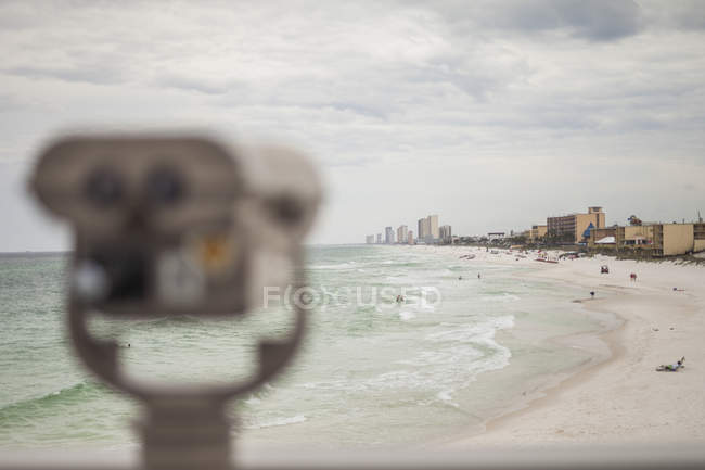 Panama city beach with blurred binoculars in foreground and buildings on background, Florida, USA — Stock Photo