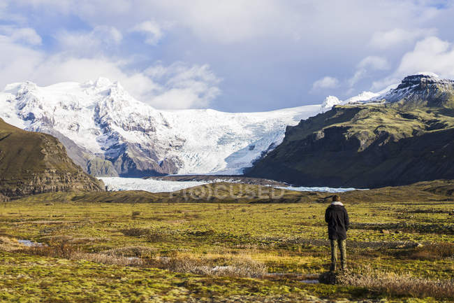 Man traveling around countryside with glacier and standing on meadow, Skaftafell, Iceland, Europe — Stock Photo
