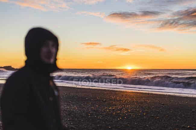 Jovem viajante ver um nascer do sol em pé na praia em Vik, Islândia, Europa — Fotografia de Stock