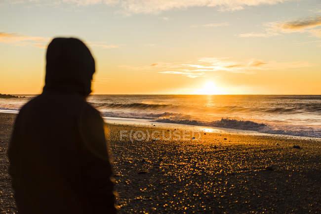 Jeune voyageur regarder un lever de soleil à Vik, Islande, Europe — Photo de stock