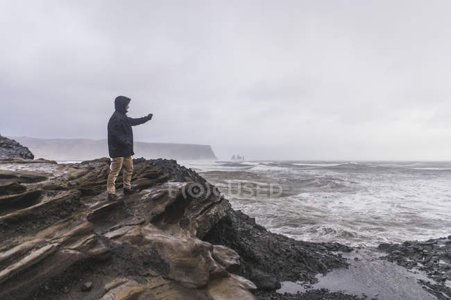 Jeune voyageur debout sur la pierre au rivage à Vik, Islande, Europe — Photo de stock