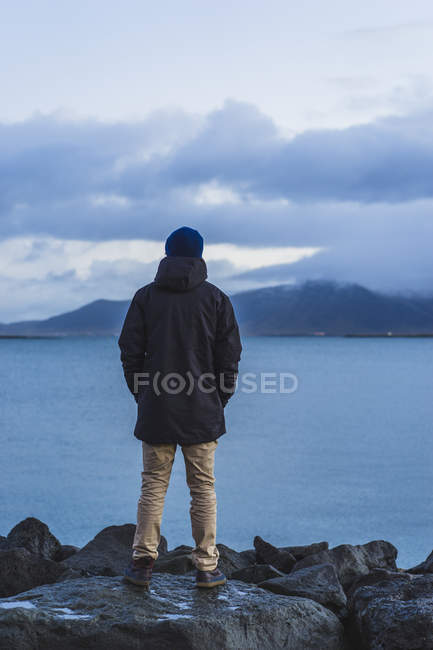 Homme debout sur le front de mer à Reykjavik, voyageant autour de l'Islande, Europe — Photo de stock