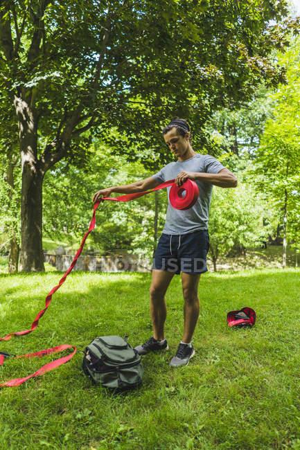Hombre Atlético de slackline en el parque en el césped - foto de stock