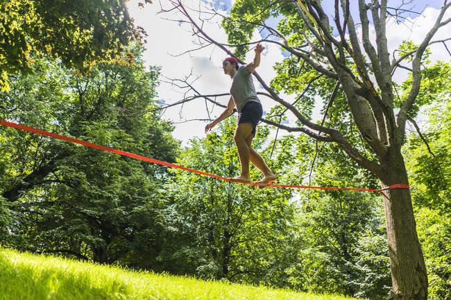 Deportiva hombre caminando de slackline en el parque entre los árboles durante el día - foto de stock