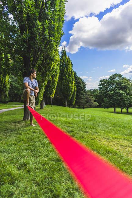 Deportiva hombre tratando de slackline en el parque y junto a árbol con la cuerda en el frente - foto de stock