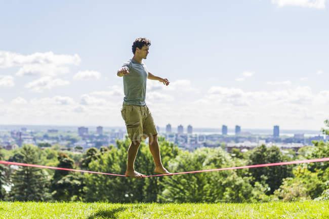 Hombre atlético caminando sobre slackline en el parque entre los árboles con la ciudad moderna sobre fondo - foto de stock