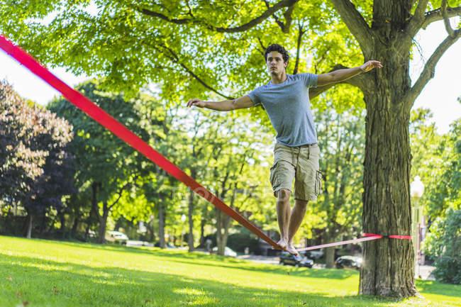 Deportiva hombre caminando de slackline en el parque entre los árboles con los brazos extendidos durante el día - foto de stock