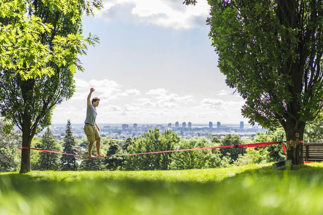 Sport homme marchant sur la slackline dans le parc entre les arbres pendant la journée — Photo de stock