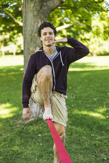 Hombre Atlético de slackline en el parque mientras está parado por una pierna en la cuerda - foto de stock