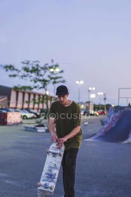 Sportliche Teenager Skateboarder Skate im Skatepark über Parkplatz Hintergrund halten — Stockfoto