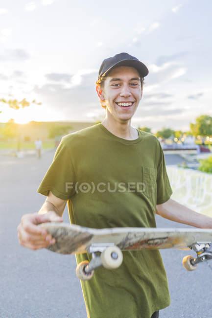 Porträt des jungen Skater Skateboard während Sonnenuntergang im Skatepark zu halten — Stockfoto