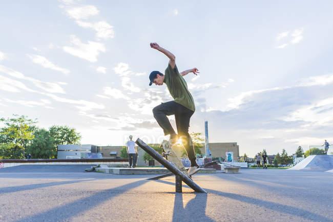 Sportliche Teenager Skateboarder einen Ollie im Skatepark zu tun — Stockfoto