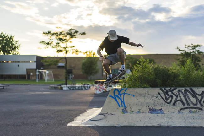 Sportliche Teenager Skateboarder Ollie im Skatepark zu tun — Stockfoto