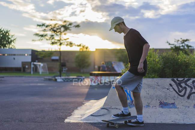 Jugendlicher Skater Skateboard im Skatepark Bein festhalten — Stockfoto