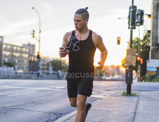Athletic man running and listening music in downtown scene, Montreal, Quebec, Canada — Stock Photo