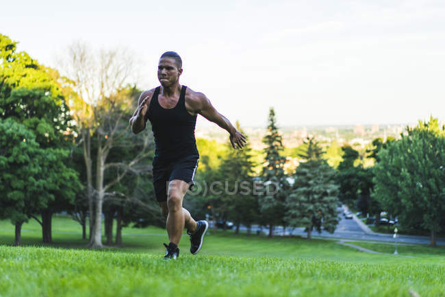 Athletic man running up hill — Stock Photo
