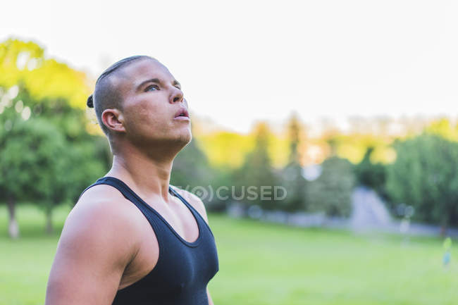 Portrait of looking up athletic man  exhausted from training in urban park — Stock Photo