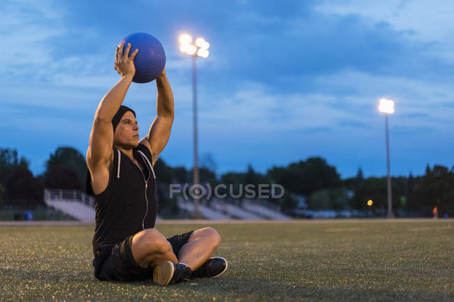 Athletic man using medicine ball during work out at night — Stock Photo