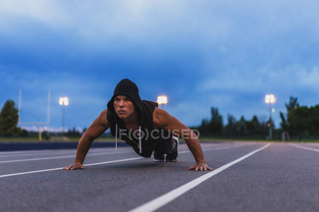 Athletic man doing push ups while working out on track at night — Stock Photo
