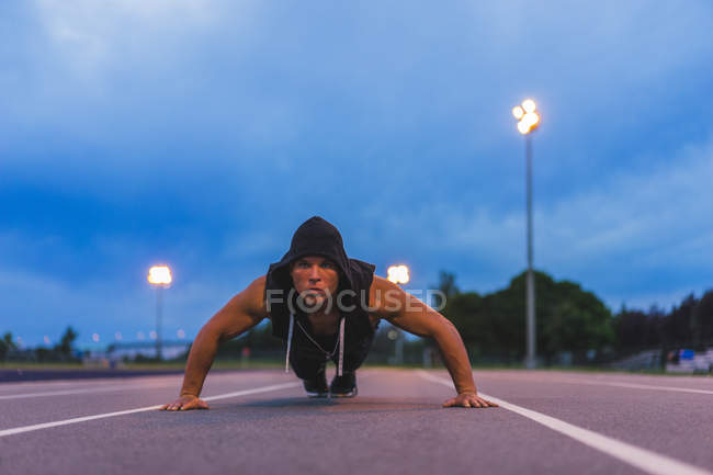 Athlet doing push ups while working out on track at night — Stock Photo