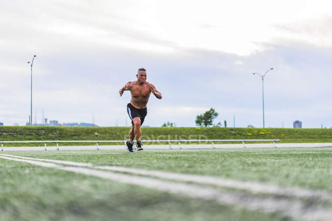 Athlet man sprinting while working out on track — Stock Photo