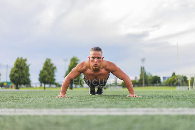 Athletic man doing push ups while working out on field — Stock Photo