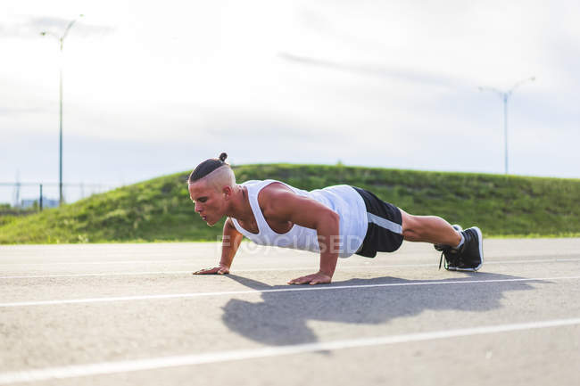 Athlet push uping while working out on track during summer — Stock Photo