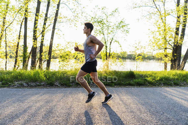 Side view of young man running in park during sunset — Stock Photo