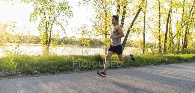 Side view of Athlet man running during sunrise — Stock Photo