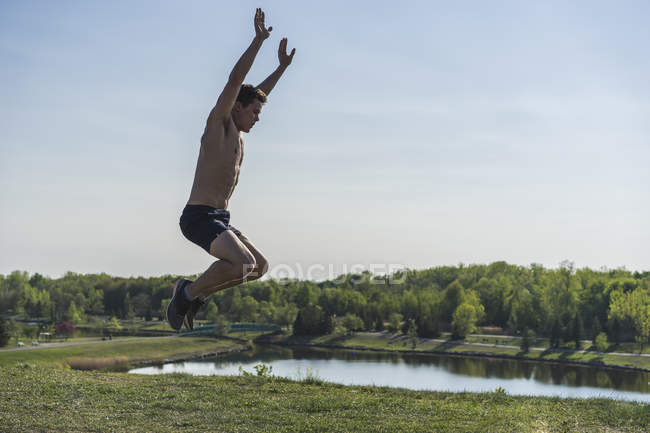 Athlet performing a burpee over park landscape — Stock Photo